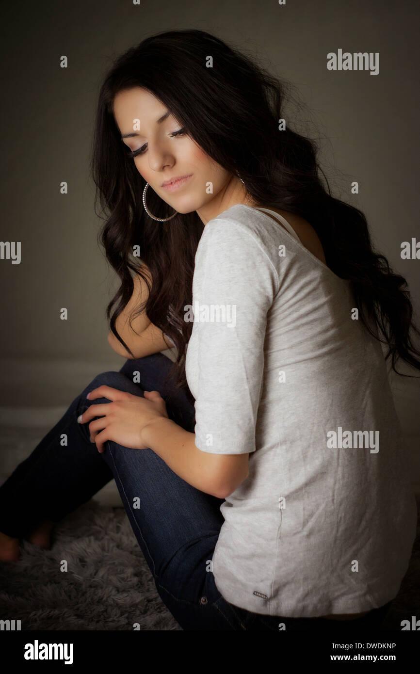 Ruhige und friedliche Szene mit schönen jungen Frau sitzt am Boden und auf der Suche nach unten. Stockbild