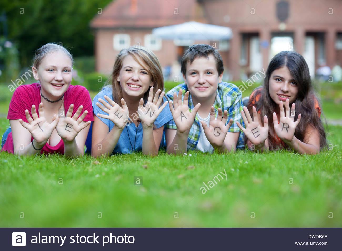 Drei Mädchen und ein Junge, die zusammen die Wort Teenager auf ihre Handflächen zeigen Stockfoto