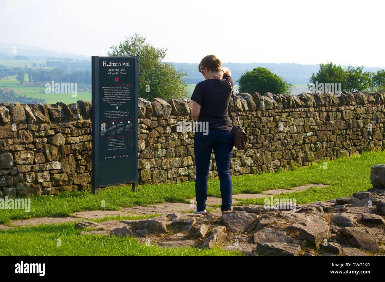 Touristen auf der Suche bei Banken Osten Turm Hinweisschild, Hadrianswall Northumberland England Großbritannien Stockfoto