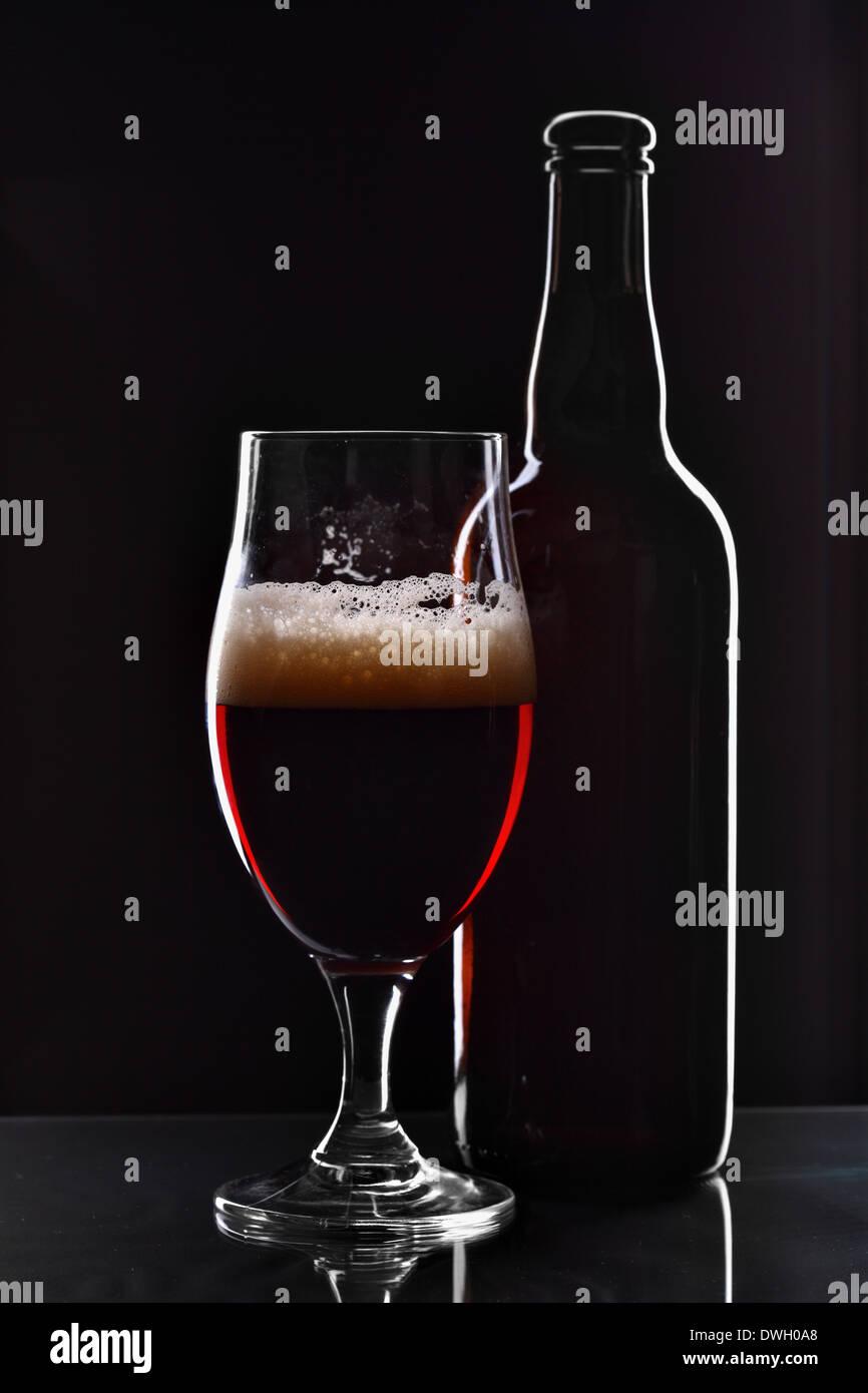 Bierflasche und Glas auf schwarzem Hintergrund Stockbild