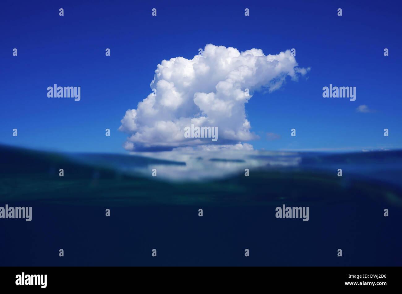 Blauer Himmel und Meer geteilt durch die Wasserlinie mit einer Wolke, die sich auf Wasser des karibischen Meeres spiegeln Stockbild