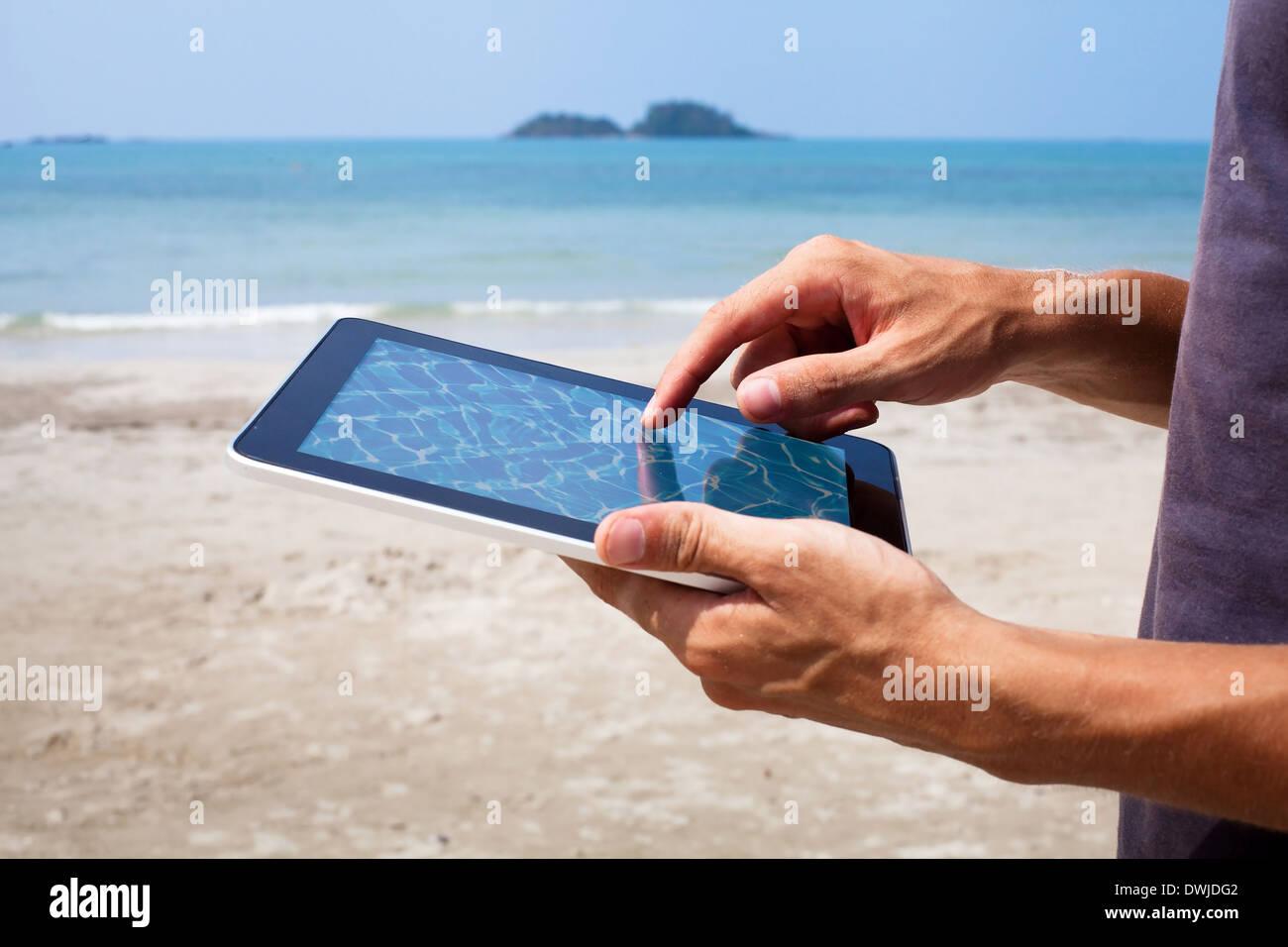 Hände mit Tablet am Strand Stockfoto