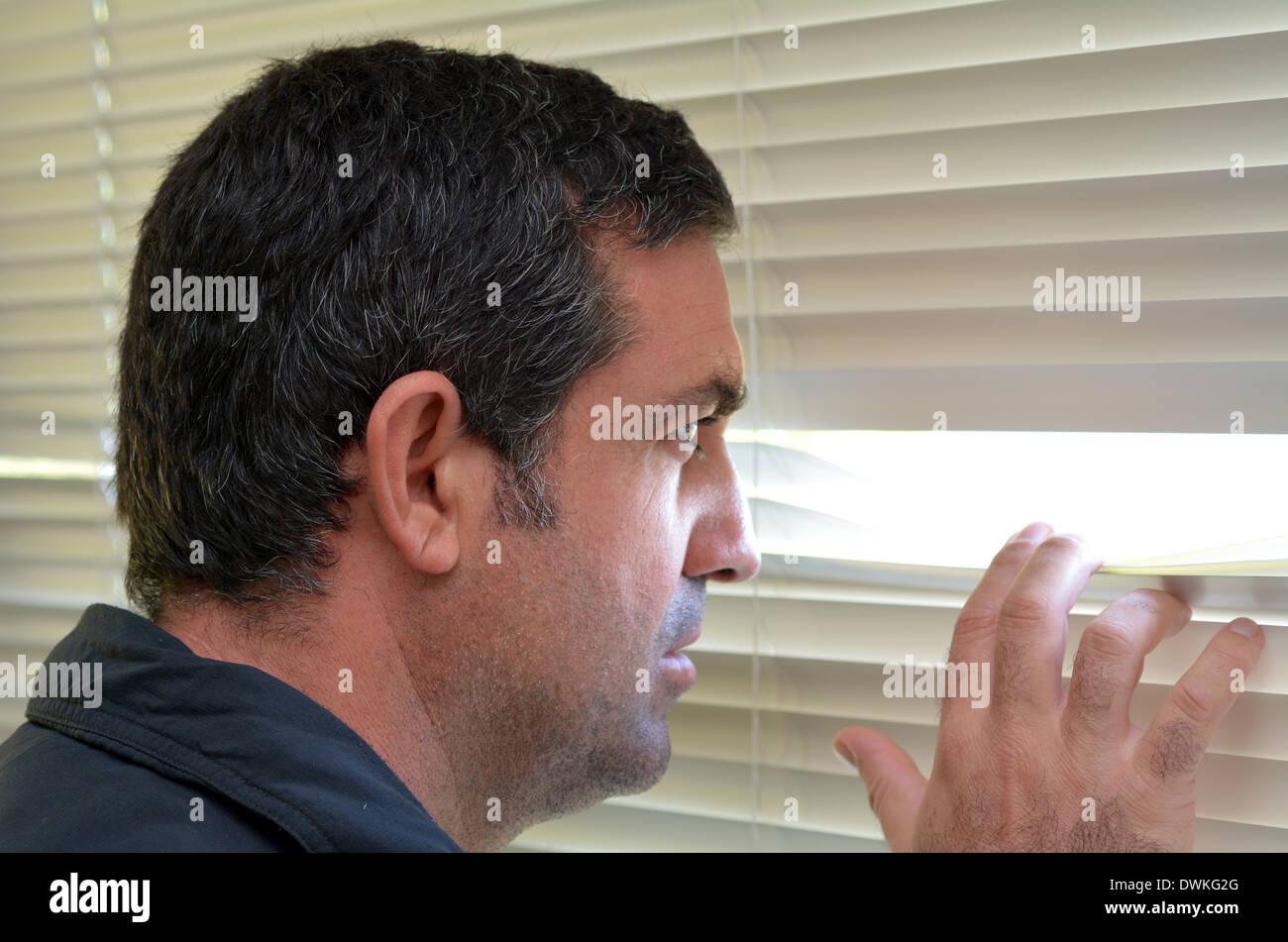 Mann (Alter 35-40) blickt durch Jalousien. Konzept-Foto von neugierig, Spion, neugierige Menschen. Stockbild