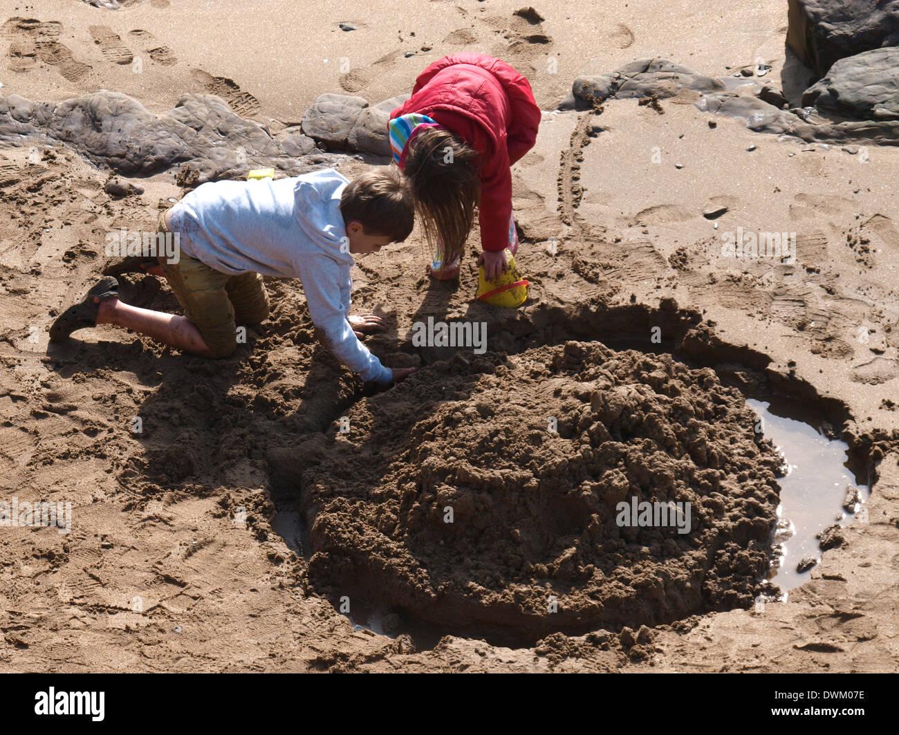 bruder und schwester bauen eine sandburg am strand auf einem