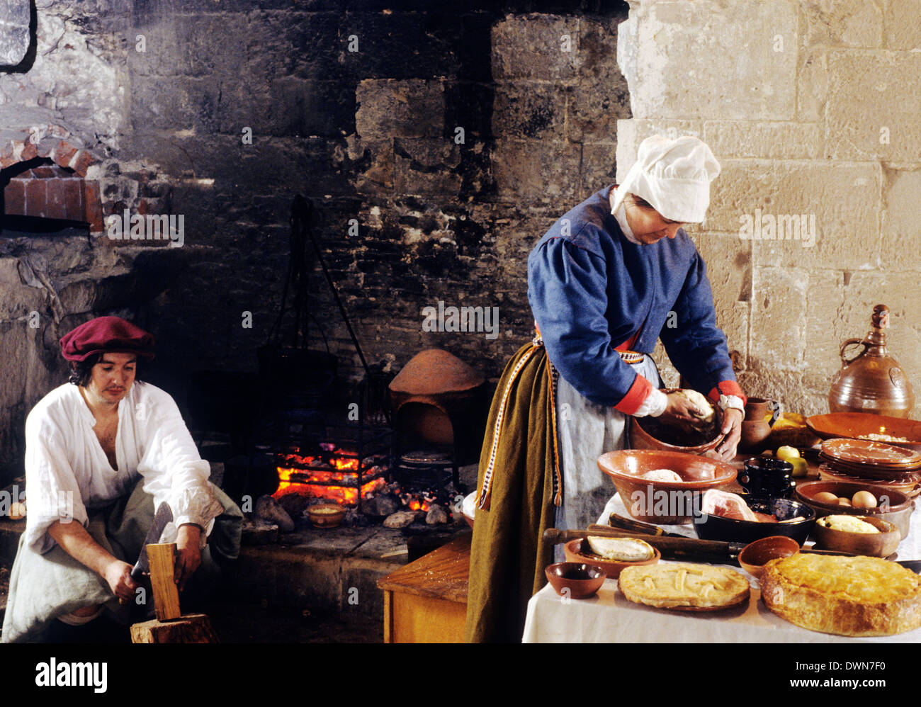 Tudor Periode Küche, Ende des 16. Jahrhunderts Reenactment Frau bereitet Essen Mann Feuer Kostüme Kostüm Stockbild