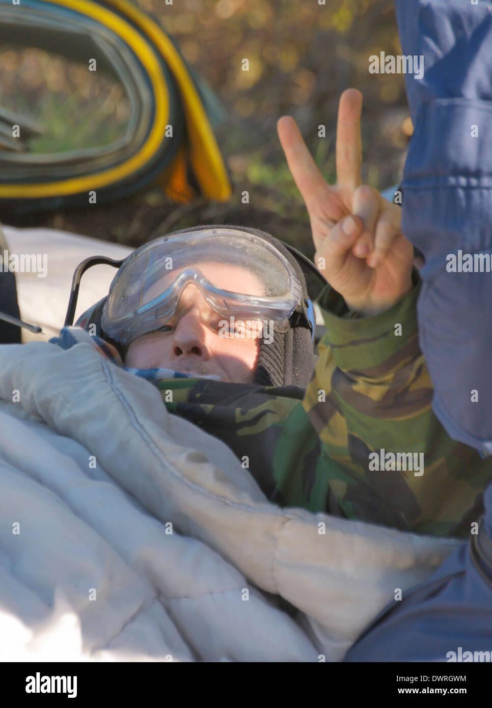 """Demonstrant Victory-Zeichen zu geben, während ein """"Lock-on"""" Gerät entfernt wird. Stockbild"""
