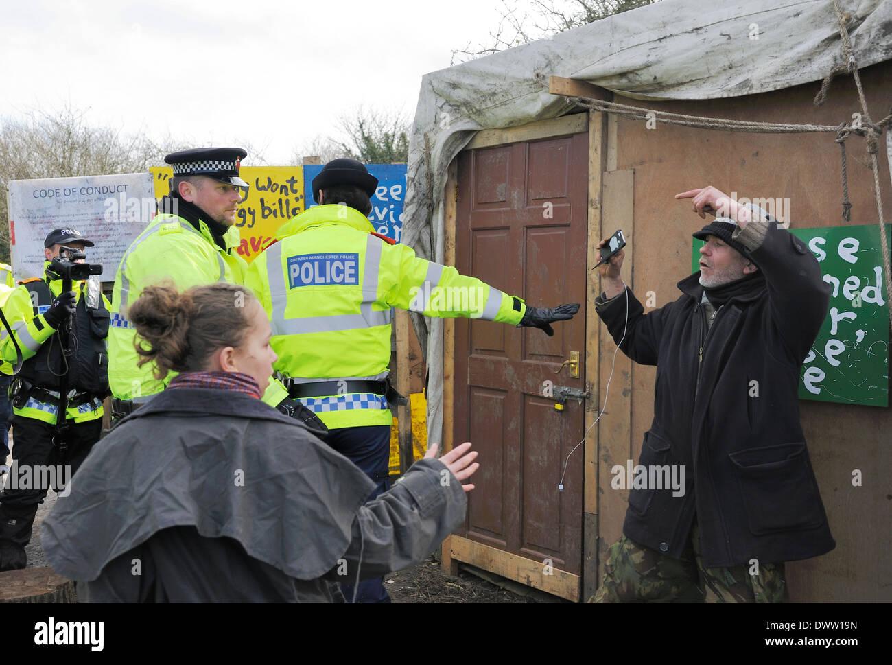 Polizistin steht vor ein Demonstrant, ihn von einem TAU-Offizier zu schützen, die ihn heftig in den Holzschuppen geschoben. Stockbild