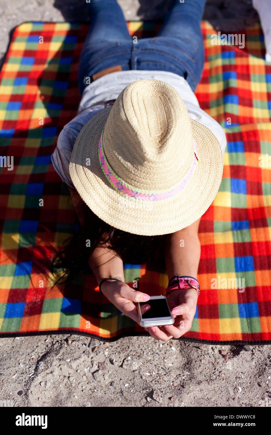 Erhöhte Ansicht von Frau mit Handy beim liegen auf der Picknickdecke Stockbild