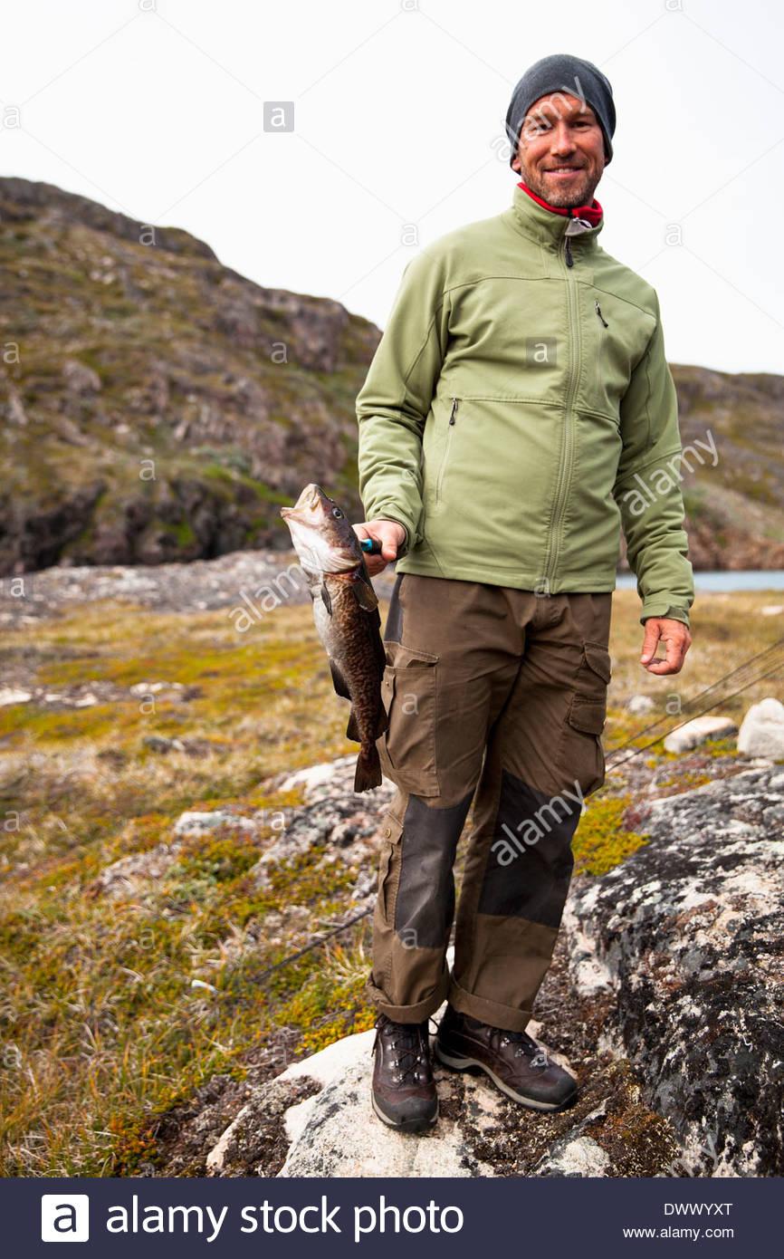 In voller Länge Portrait von reifer Mann in warme Kleidung, Fisch im freien hält Stockbild