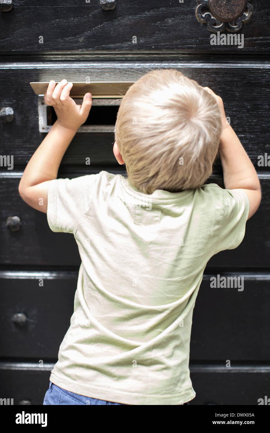 Rückansicht des kleinen Jungen Mailslot Tür Durchsicht Stockbild