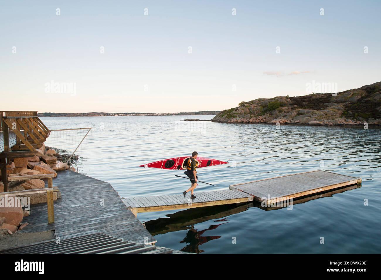 Gesamte Länge der Mann trägt Kajak während des Gehens auf Pier Fluss Stockbild
