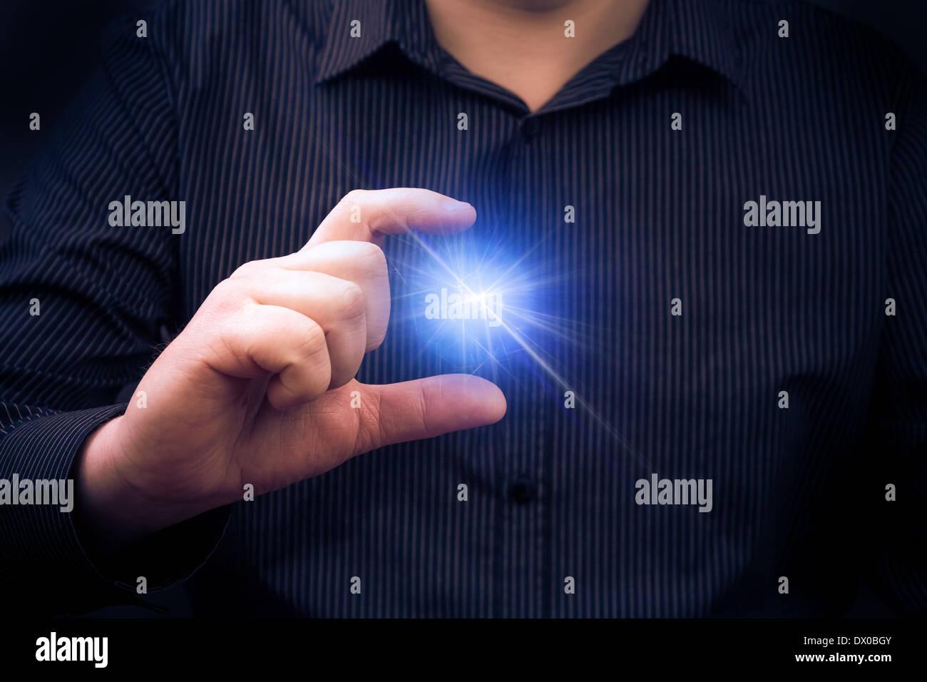 Auf mysteriöse Weise emittierende macht in der Hand eines Mannes Stockbild