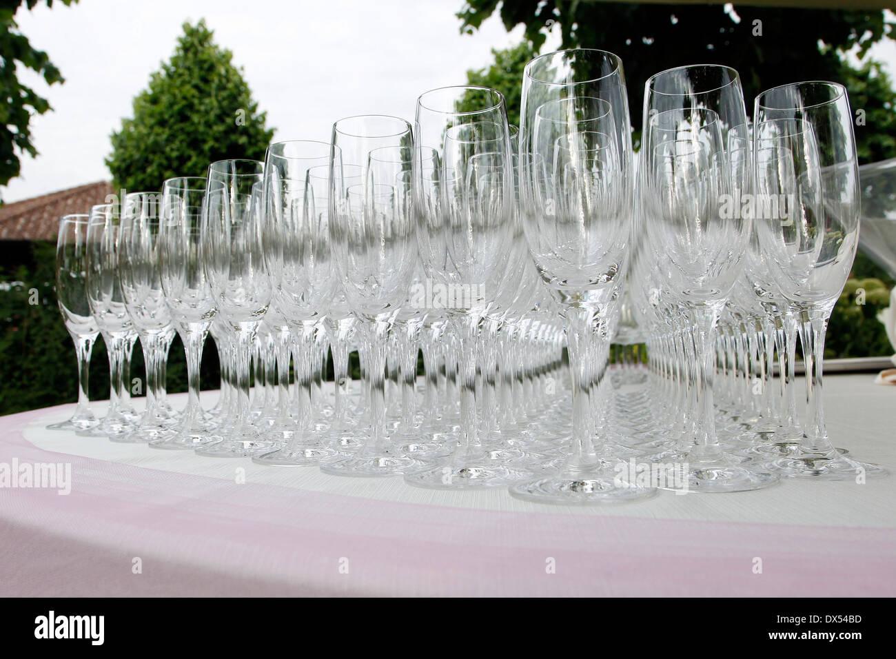 Weingläser, aufgereiht auf einem Tisch Stockbild