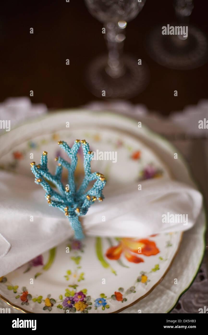 Blaue Korallen Serviettenring auf Blumen Teller, Gedeck, erhöhte Ansicht Stockbild