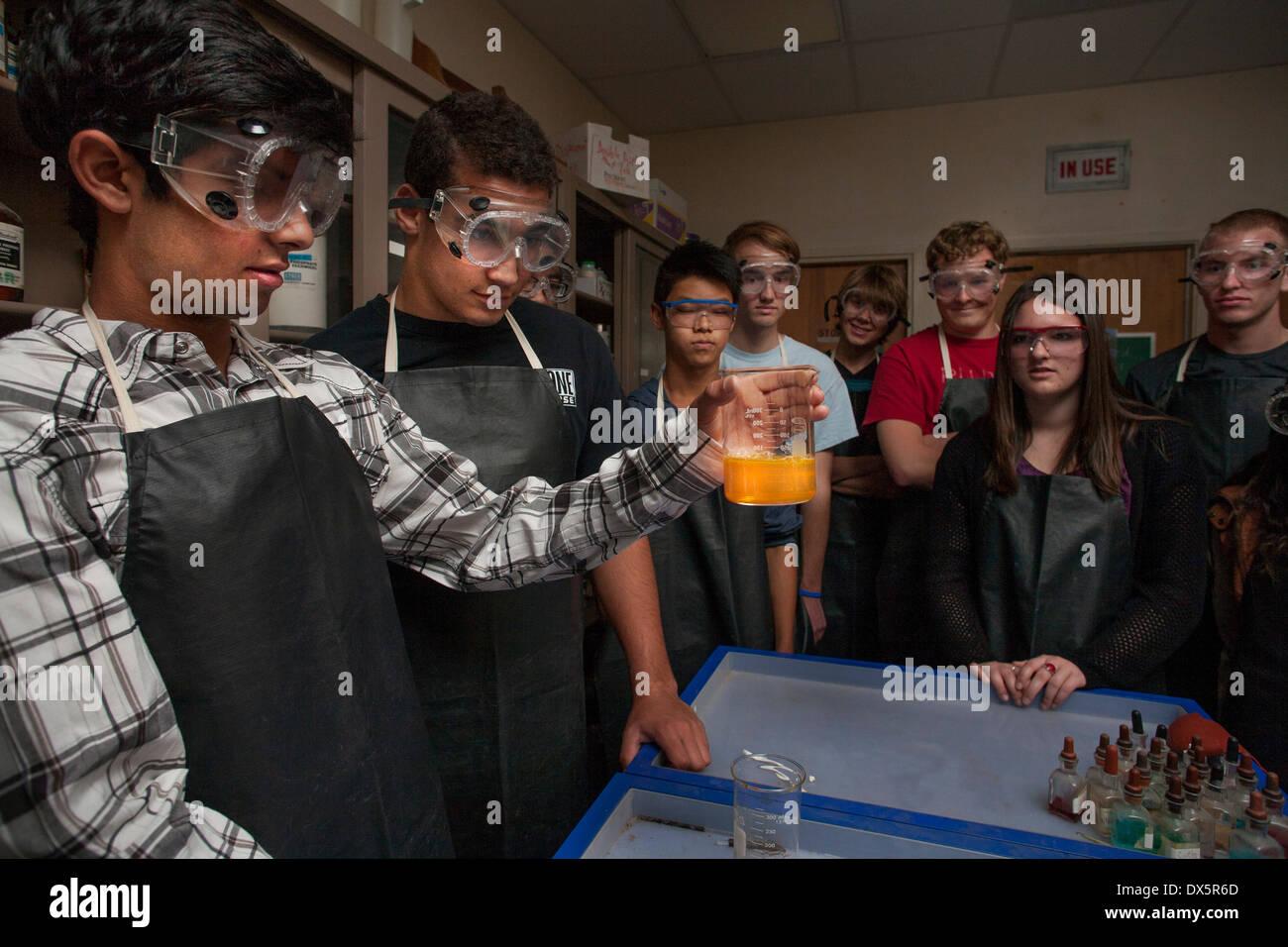 Gemischtrassig San Clemente, CA, produzieren Wissenschaft Gymnasiasten Biolumineszenz in einer Dunkelkammer durch Mischen Kaliumferrocyanid, Wasserstoffperoxid und energetische Licht-Lösung in ein Becherglas, eine cremefarbene Leuchten zu produzieren. Hinweis: Sicherheit Schürzen und Schutzbrillen. Stockfoto