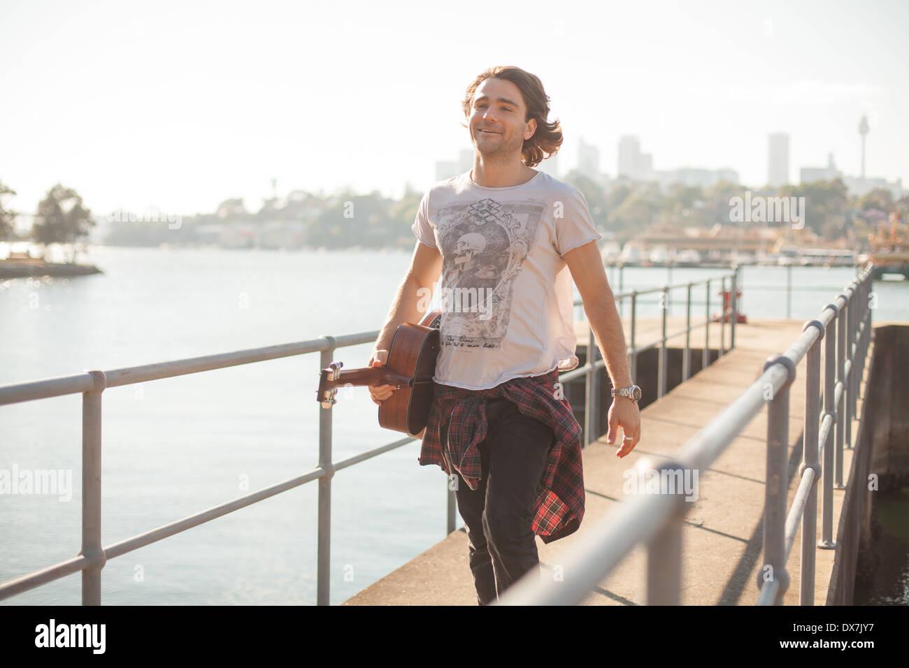 Ein gesunder junger Mann durch das Wasser im Hafen von Sydney mit seiner Gitarre Stockbild