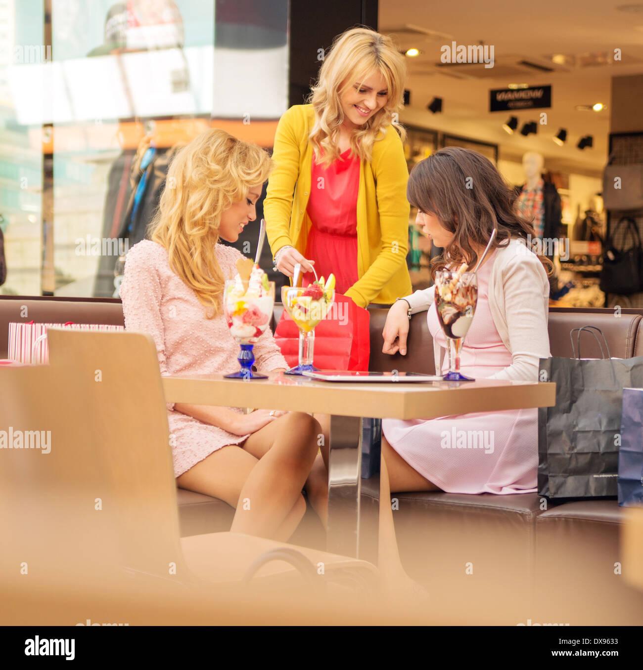 Drei junge fröhliche Freundinnen in der kurzen Pause Stockbild