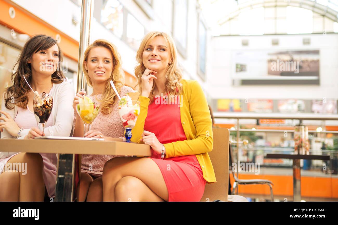 Lächelnden Freundinnen genießen ihre süße Nachspeise Stockbild