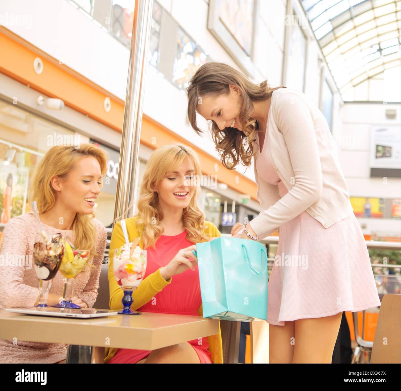 Attraktive Dame zeigt ihre Freundinnen einige Sachen Stockbild