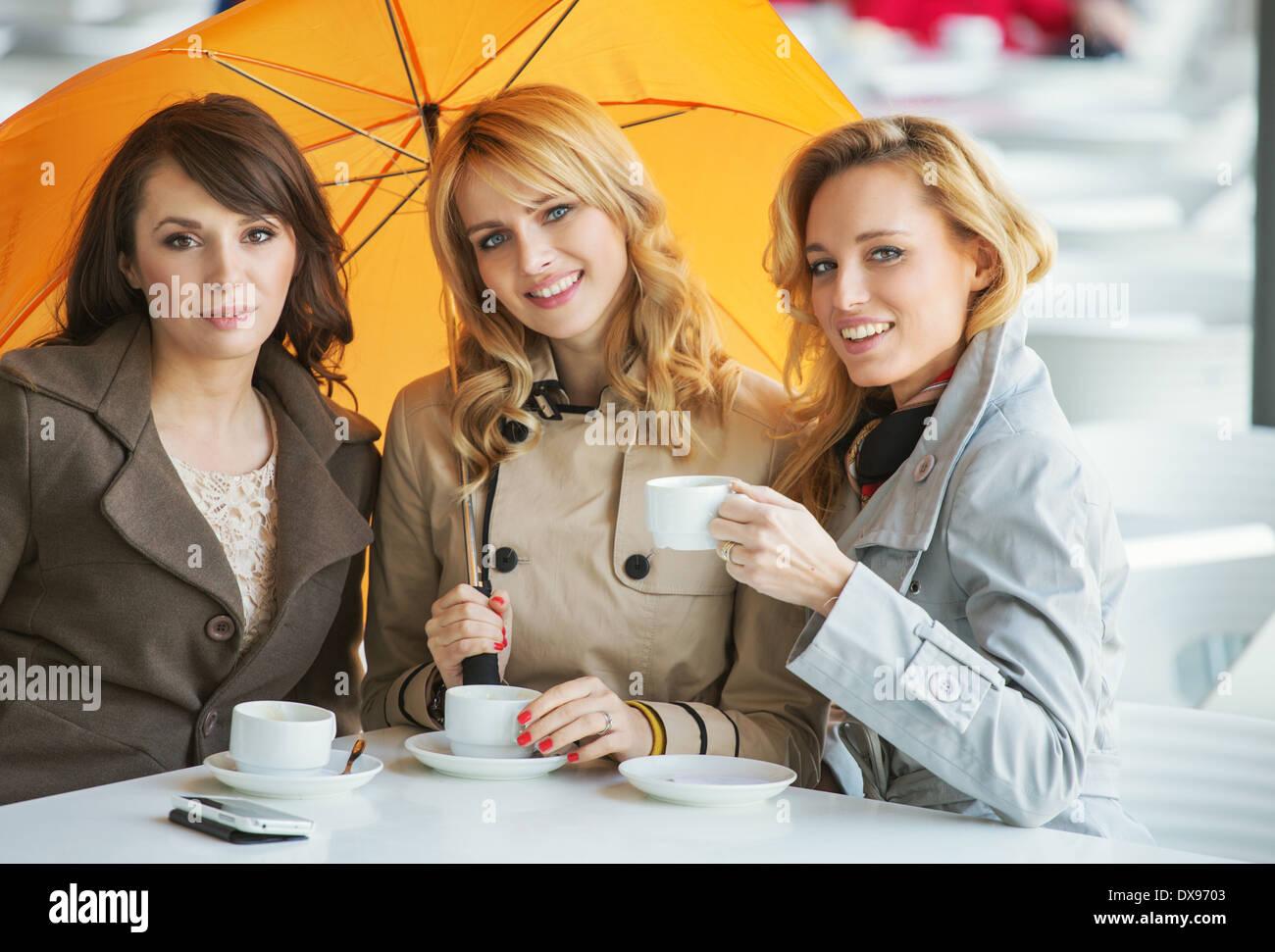 Drei hübsche Frauen, der Kaffee und der Regenschirm Stockbild