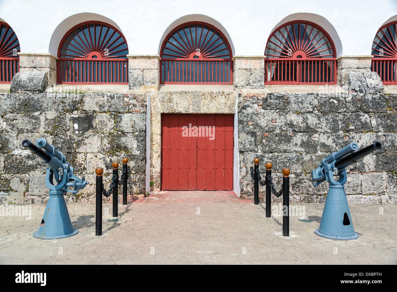 Gebäude im Kolonialstil in Cartagena/Kolumbien mit zwei großen Kanonen davor Stockbild
