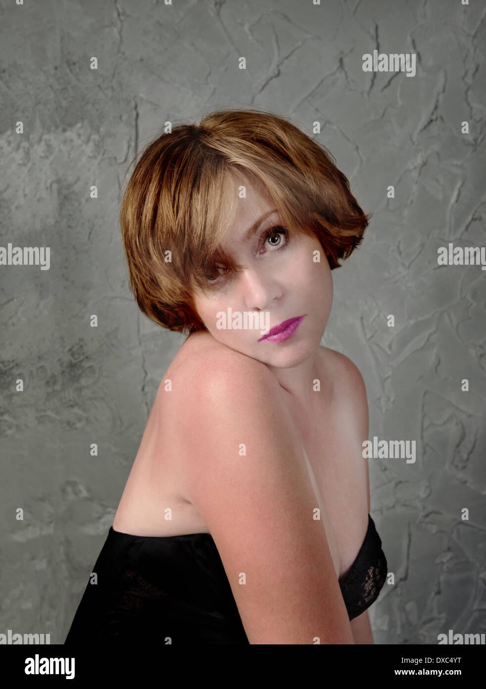 Portrait der schönen Frau in einer Melancholie auf Grunge-Wand-Hintergrund Stockfoto