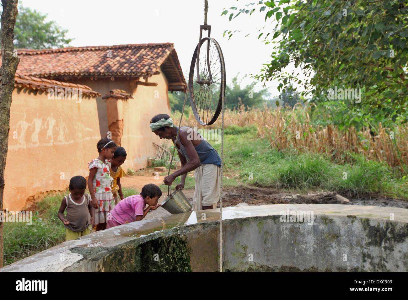 Kinder Trinkwasser aus dem Brunnen geholt. Hardhekitand Dorf, Dist Bokaro, Jharkhand, Indien Stockbild