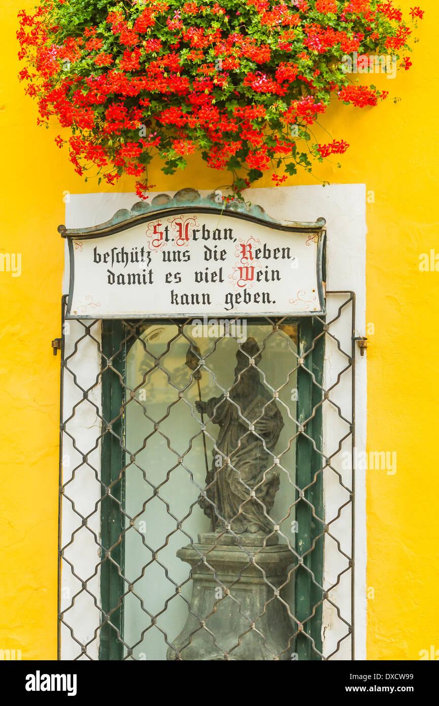 Blume geschmückt Alkoven am Gebäude des Weinguts Reinprecht mit einer Statue von st. urban und eine Gedenktafel Stockbild