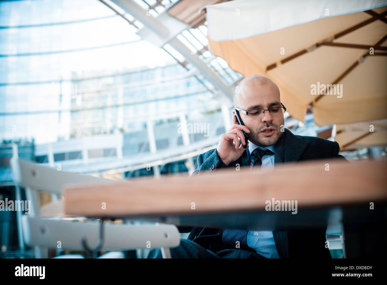 elegante modische Geschäftsmann auf dem Handy an der bar Stockbild