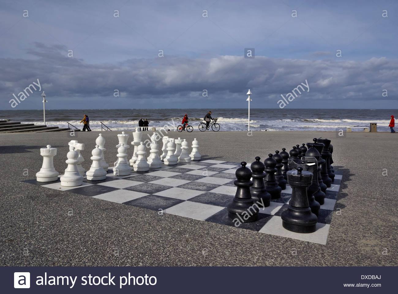 Menschen sitzen, radeln und spazieren Sie am Meer in Norderney, großes Schachbrett im Vordergrund. Stockbild