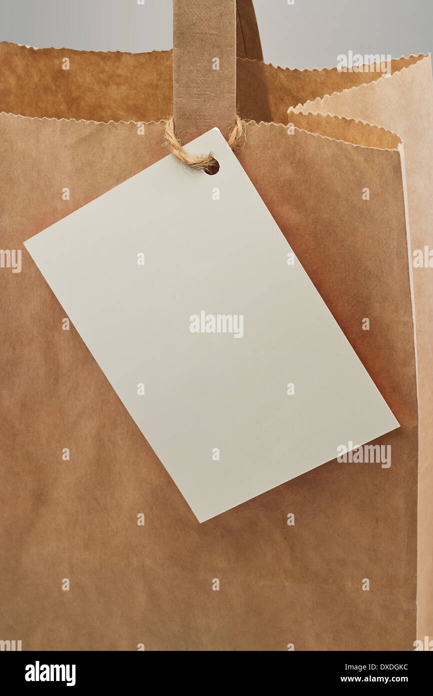 Braune Papiertüte mit leeren Tag für Ihre persönliche Nachricht oder Unternehmensbranding befestigt Stockbild