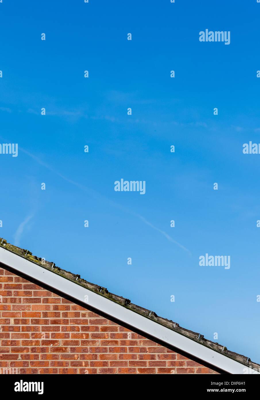 Rand des abfallenden gefliest Dach über roten Backsteinmauer gegen überwiegend blauen Himmel mit verschwommenen Wolken. Stockbild