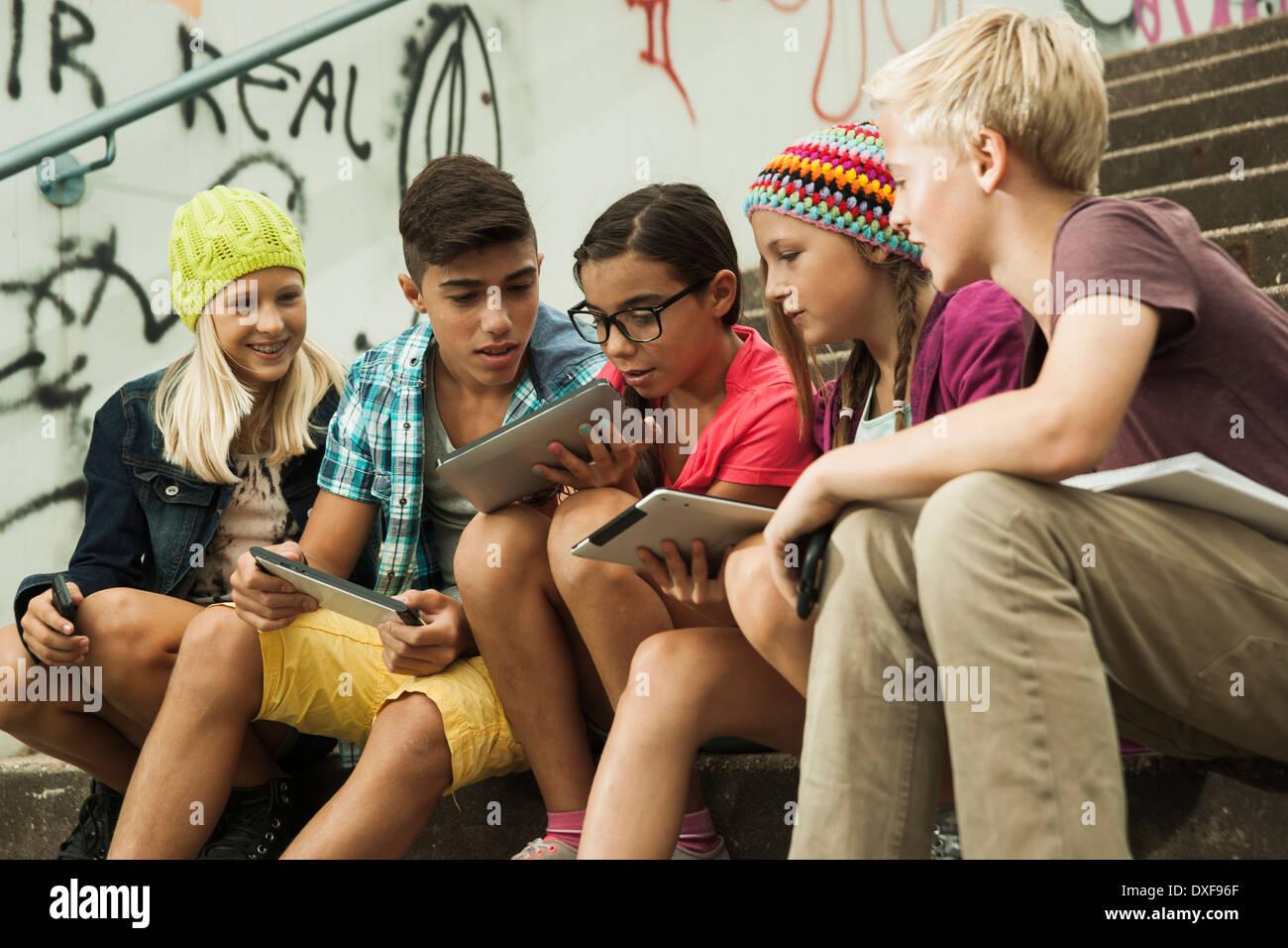 Gruppe von Kindern auf Treppen im Freien, sitzend mit Tablet-PCs und Smartphones, Deutschland Stockfoto