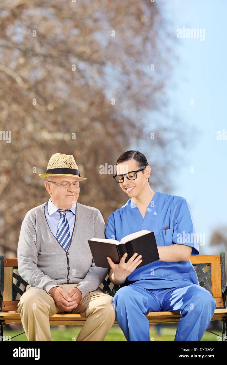 Krankenpfleger, ein Rentner im Park lesen Stockbild