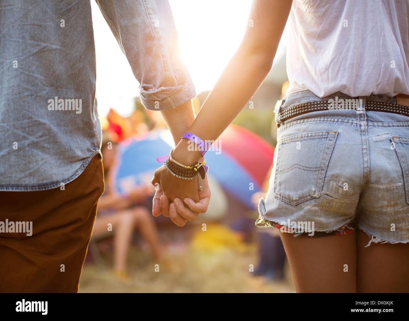 Paar Hand in Hand in der Nähe von Zelten beim Musikfestival Stockbild