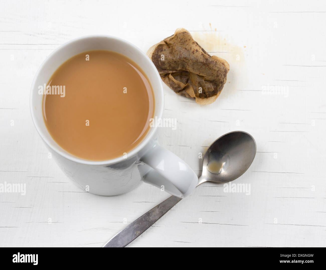 Eine Tasse starken Tee mit Milch, einen gebrauchten Teebeutel und einen Teelöffel auf weißem Hintergrund Stockbild
