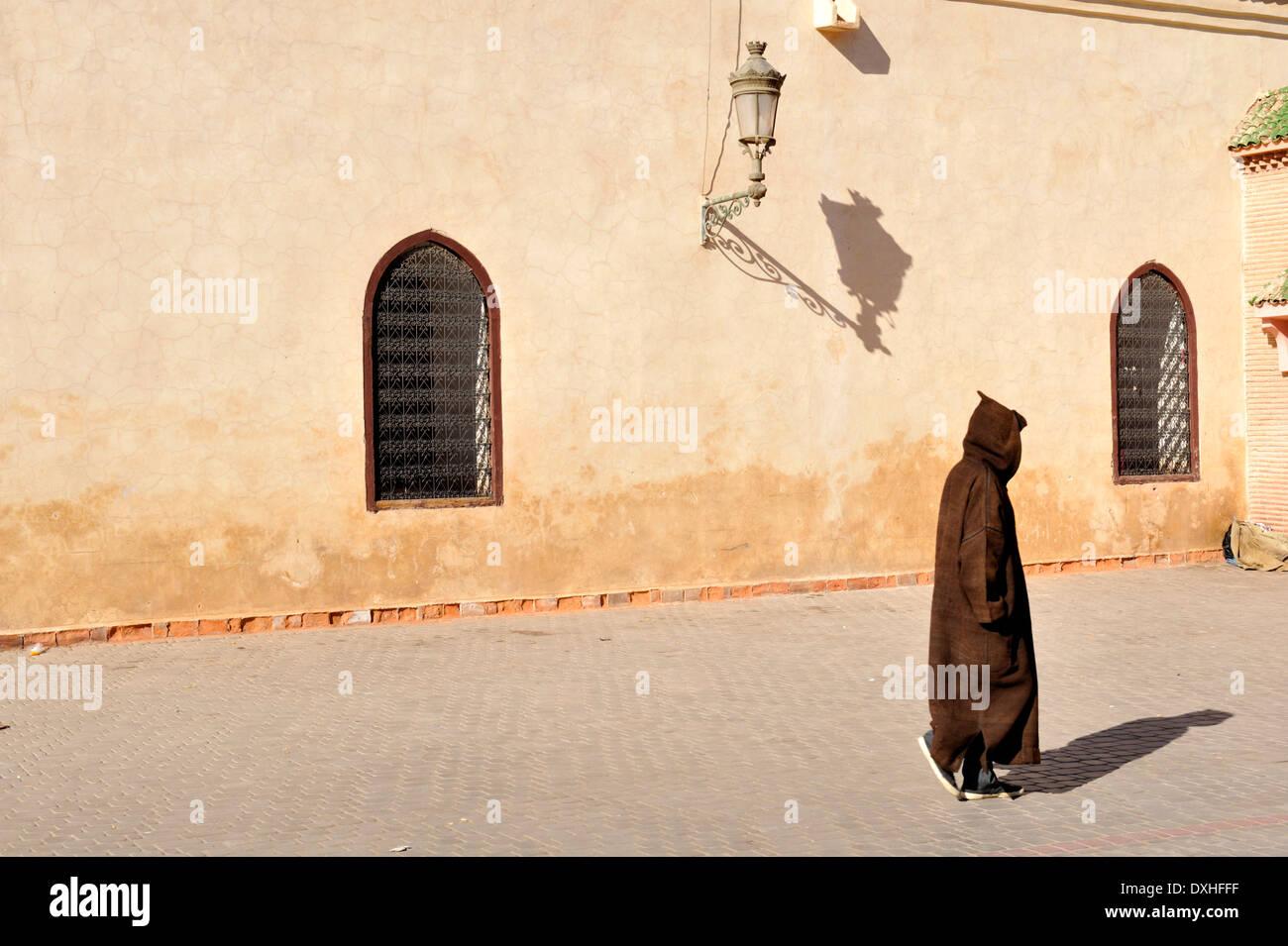 Berber, marokkanisch, Mann in traditionellen hooded Robe zu Fuß durch Wand, Marrakesch, Marokko Stockbild