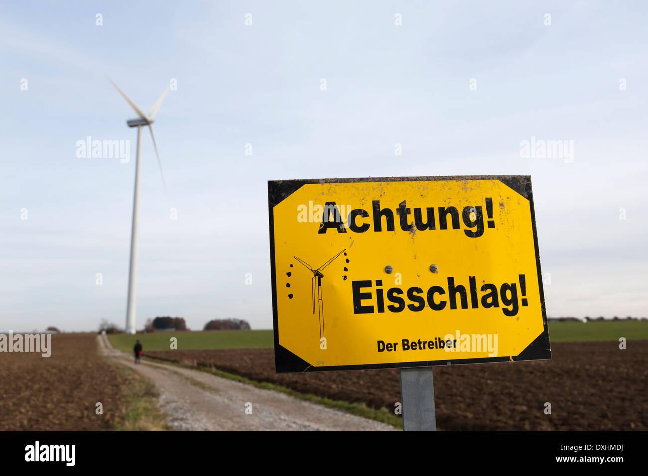 """""""Hüten Sie sich vor Eisfall"""" melden Sie vor einer Windkraftanlage Stockbild"""