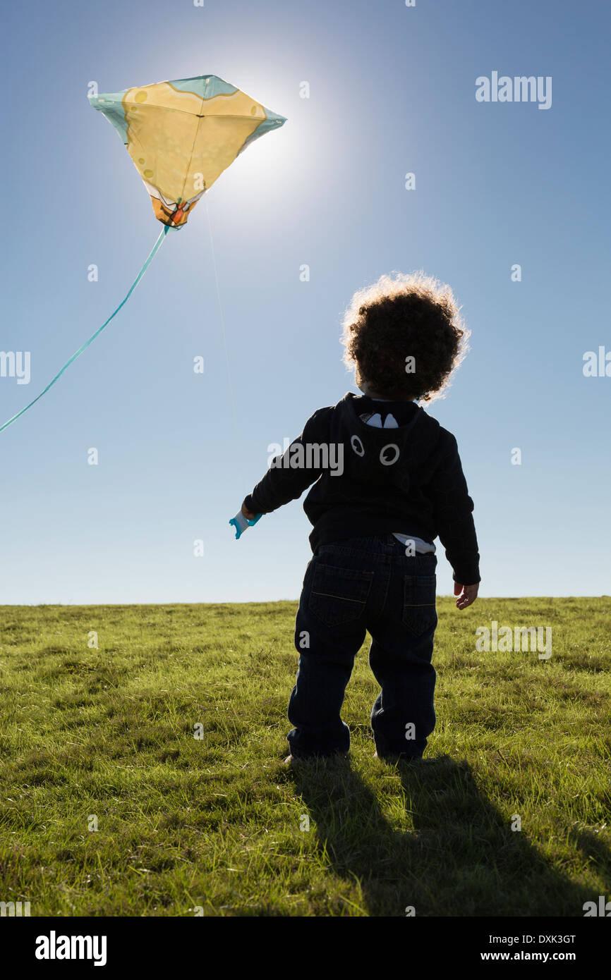 Gemischte Rassen junge beobachten Drachensteigen gegen blauen Himmel Stockfoto