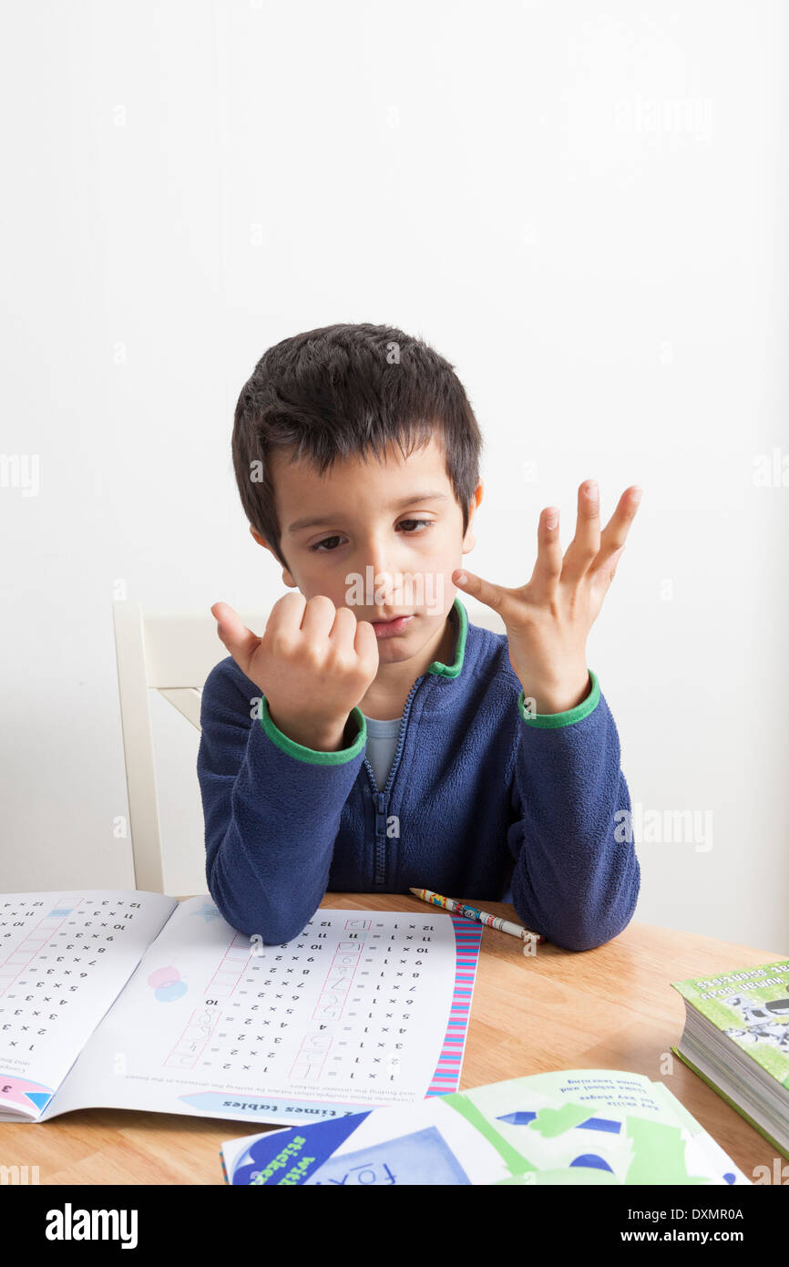 Schuljunge l an seinen Fingern zählen Stockbild