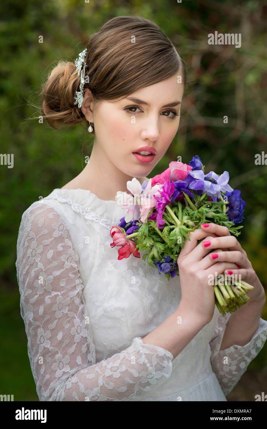 Junge Braut hält einen Strauß Wiesenblumen, Stockbild