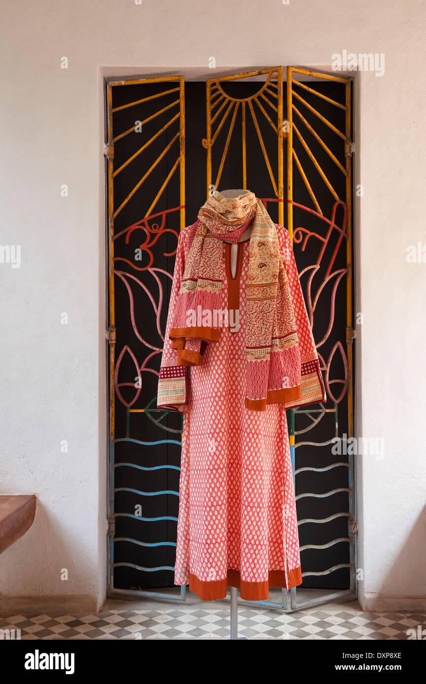 Petterned Robe hängt von ironworked Konzertina Tür im indischen Bundesstaat Goa Stockbild
