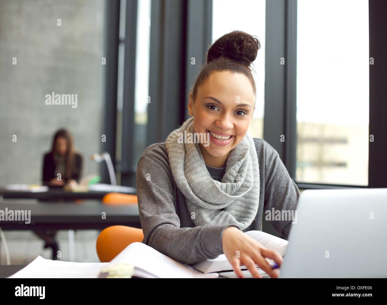 Glückliche junge Frau sitzt in der Bibliothek mit Büchern und einen Laptop-Computer, Informationen für Stockbild