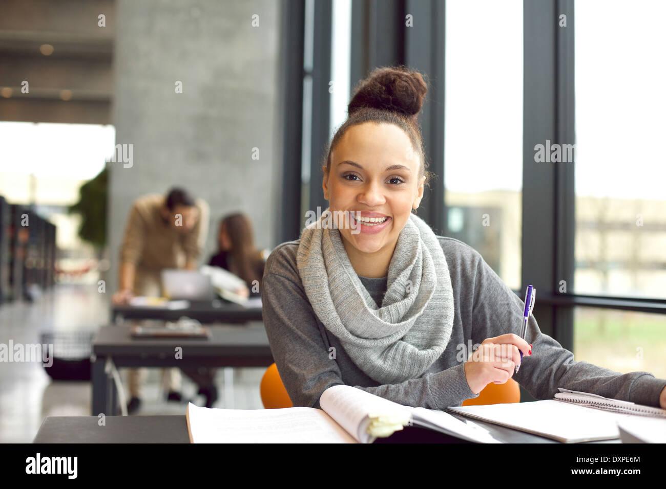 Glückliche junge Frau sitzt in der Bibliothek mit Büchern. Fröhliche junge Studentin Abschlussprüfungen vorbereiten. Stockbild