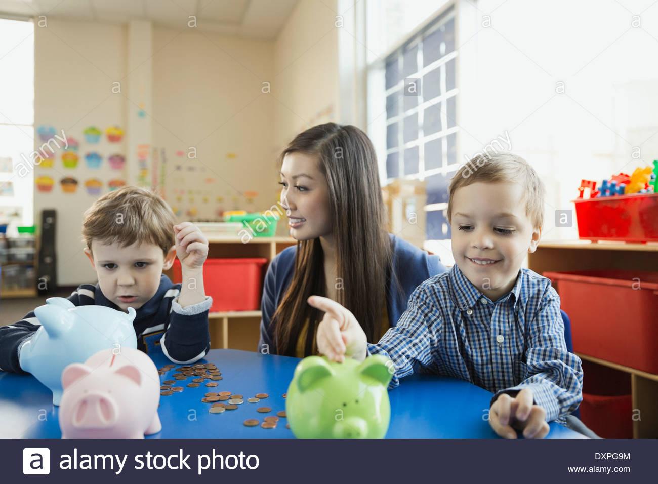 Lehrer mit Grundschüler, Geld im Sparschwein Stockbild