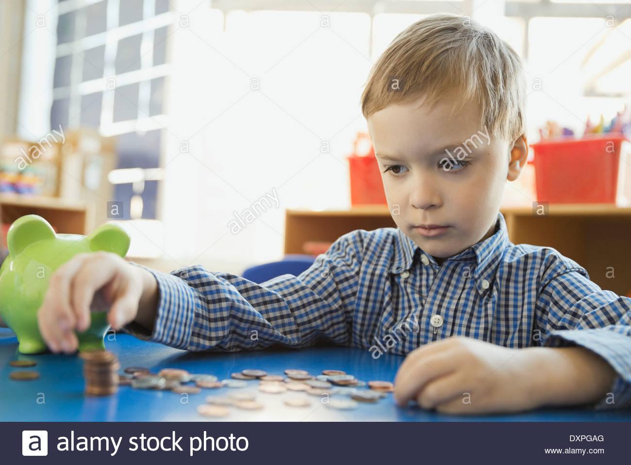 Jungen zählen Münzen in der Grundschule Stockbild