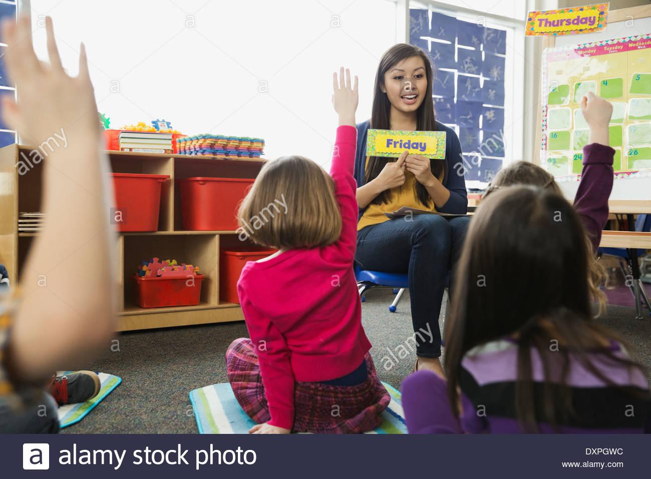 Lehrer, die Überprüfung der Wochentage mit Grundschüler Stockbild