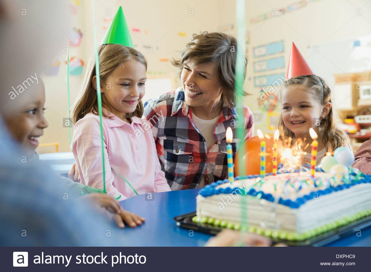 Lehrer mit Kindern feiern Geburtstag in der Grundschule Stockbild