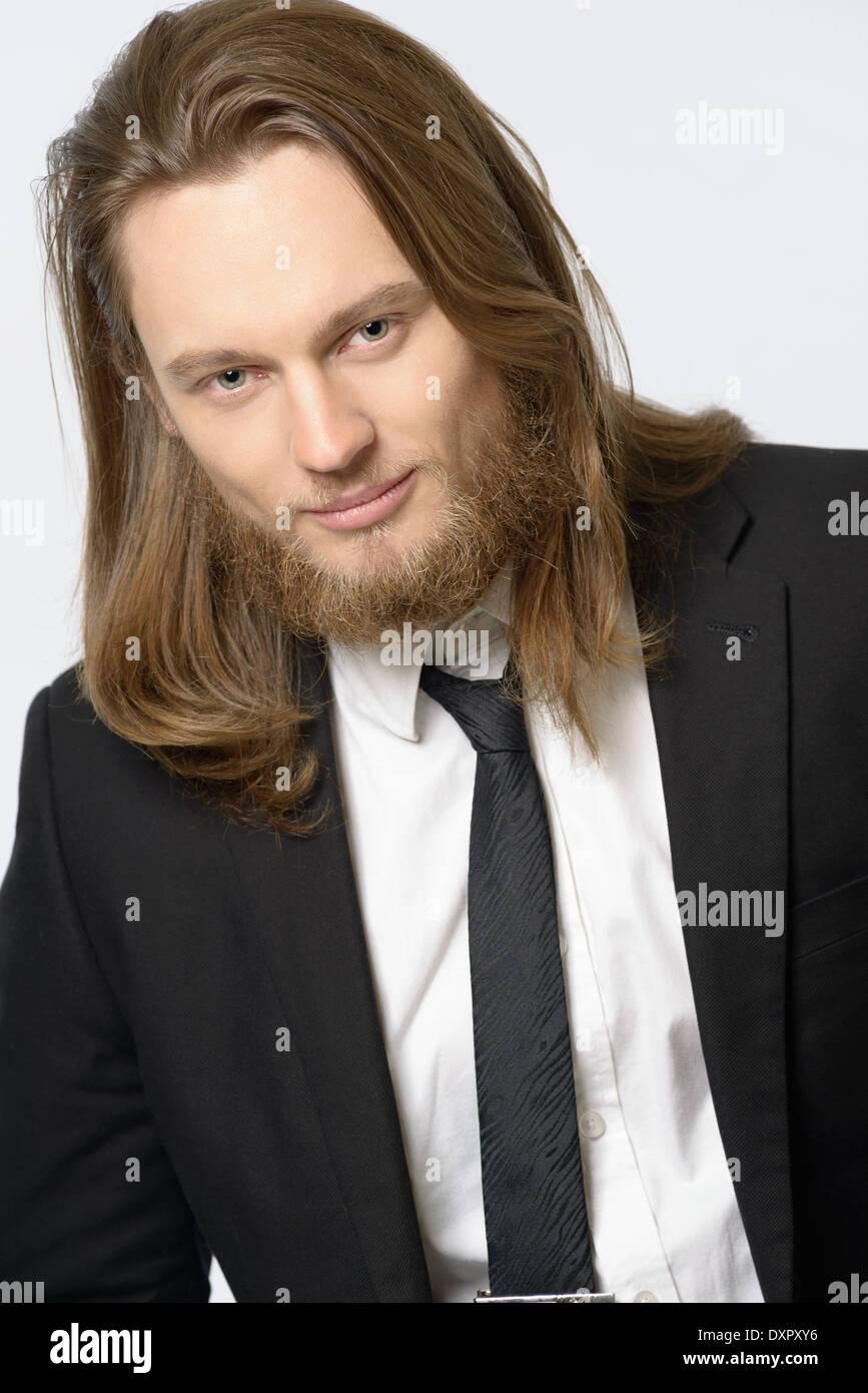 ein langhaariger mann, männermodel mit bart tragen anzug