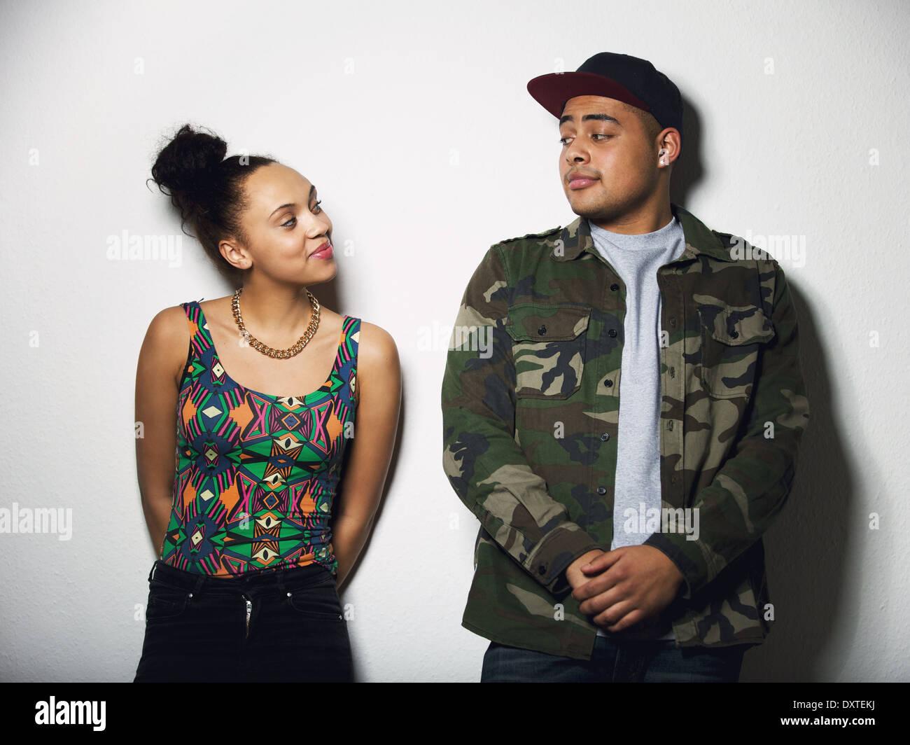 Junger Mann und Frau einander mit Haltung betrachten. Junges Paar in Freizeitkleidung auf grauem Hintergrund. Stockbild